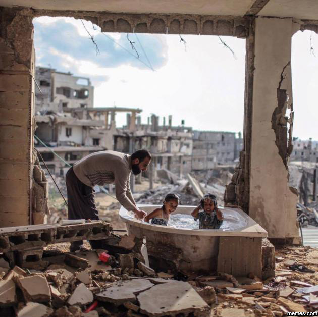 Palestinian father bathing his daughter and niece in their destroyed home.